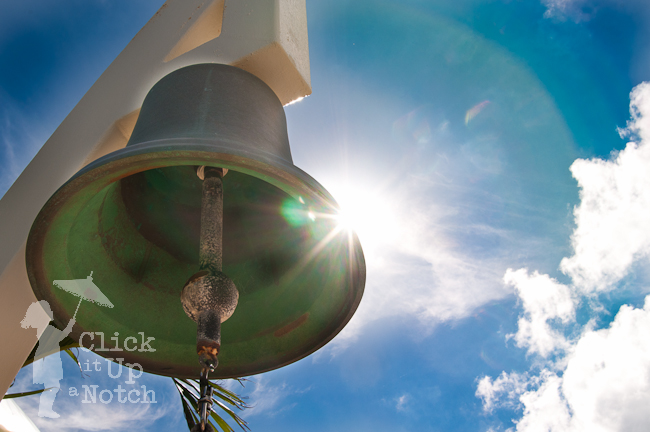A bell partially blocking the sunny of a blue sky day with clouds in the sky creating a starburst photograph.