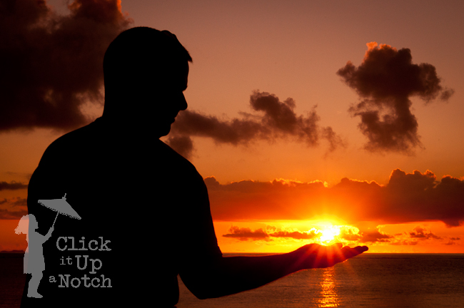 A sunset silhouette of a man holding out his hand to hold the sun that is in a starburst effect.