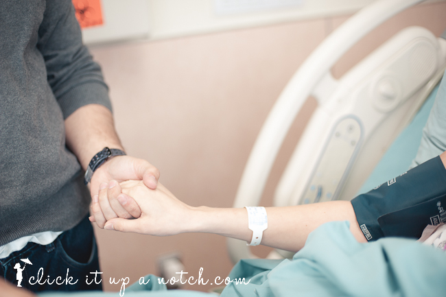 Two people holding hands in the hospital before the baby is born.