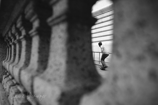 Black and white photo of a skateboarder framed by columns on the street.