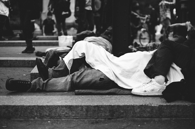 Black and white street photography of people sleeping on the street.