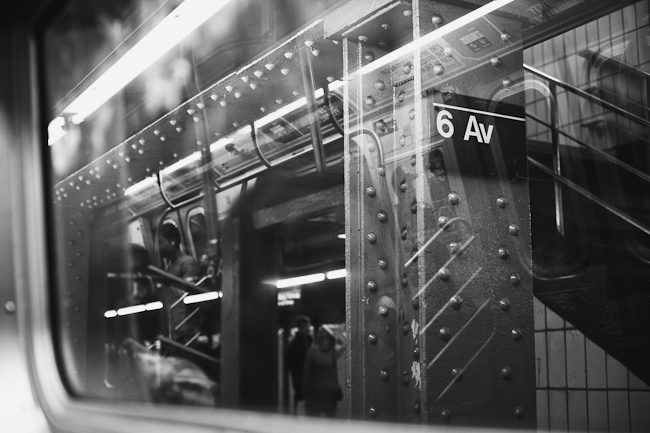 Black and white photo from the inside of a train looking out into the train station.